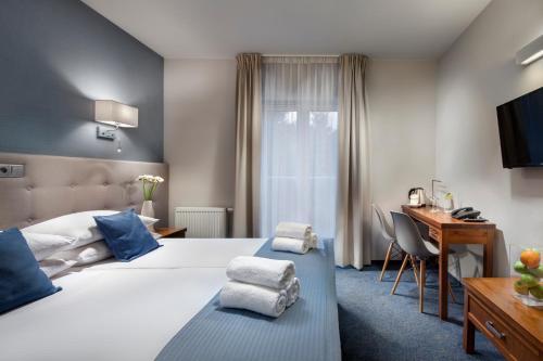 A bed or beds in a room at Hotel Aqua Sopot
