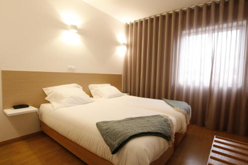A bed or beds in a room at Baixa Hotel