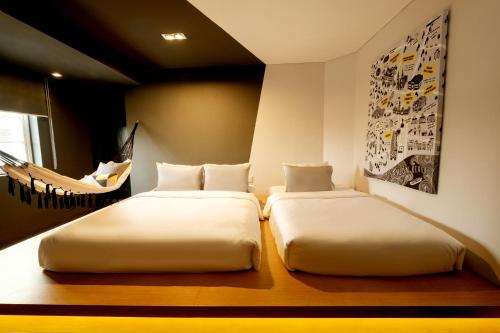 A bed or beds in a room at The Hammock Hotel Ben Thanh