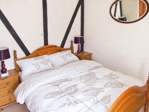 A bed or beds in a room at Mill Wheel Cottage