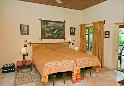 A bed or beds in a room at WelcomHeritage Maharani Bagh Orchard Retreat