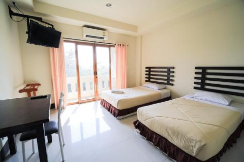 A bed or beds in a room at AmornSukhothai Hotel