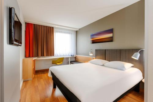 A bed or beds in a room at ibis Bremen City