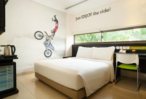 A bed or beds in a room at Grandmas Plus Hotel Seminyak