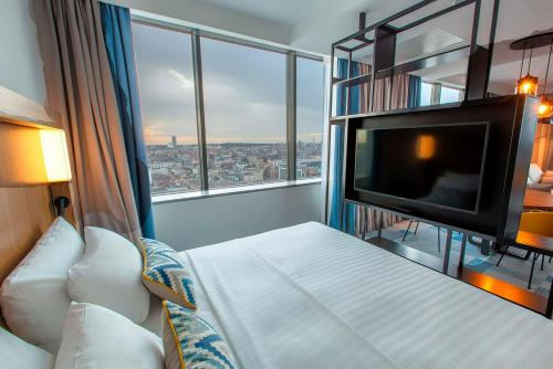A bed or beds in a room at Courtyard by Marriott Katowice City Center