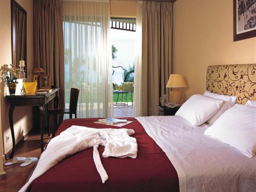 A bed or beds in a room at Grecotel Grand Hotel Egnatia