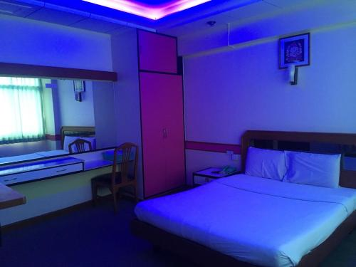 A bed or beds in a room at Taksin 2 Hotel