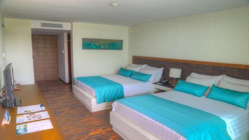 A bed or beds in a room at Estelar Playa Manzanillo - All inclusive