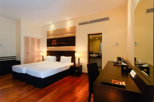 A bed or beds in a room at Renuka City Hotel