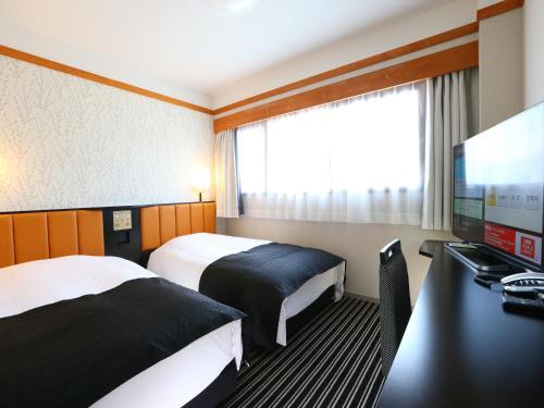 A bed or beds in a room at APA Hotel Karuizawa Ekimae Karuizawaso