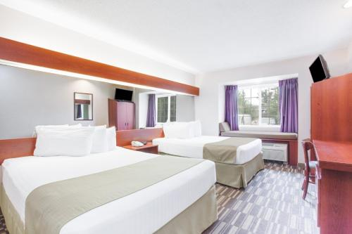A bed or beds in a room at Microtel Inn & Suites by Wyndham Olean