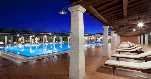 The swimming pool at or near I Giardini di Cala Ginepro Hotel Resort