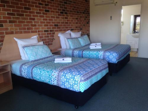 A bed or beds in a room at Inverell Terrace Motor Lodge