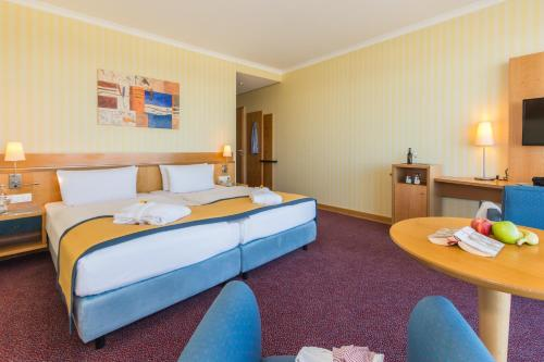 A bed or beds in a room at Strand-Hotel Hübner