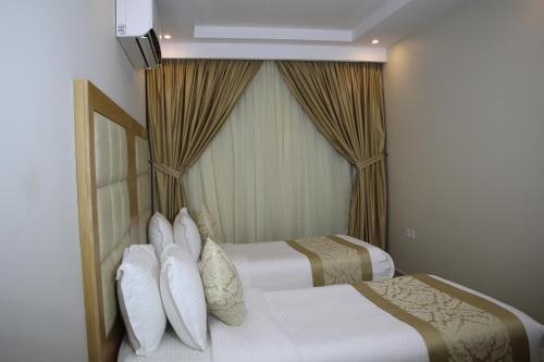 سرير أو أسرّة في غرفة في فندق المهيدب ريزيدنس الخفجي