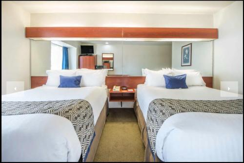 A bed or beds in a room at Microtel Inn and Suites By Wyndham Miami OK
