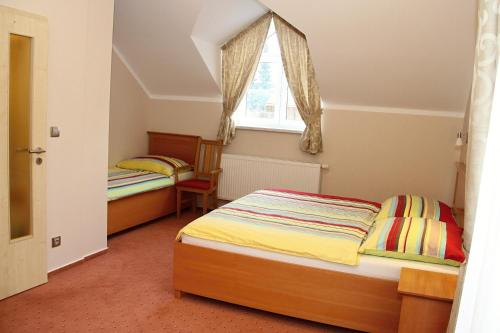 A bed or beds in a room at Penzion Harmonie