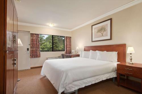 Кровать или кровати в номере Travelodge by Wyndham Vancouver Lions Gate