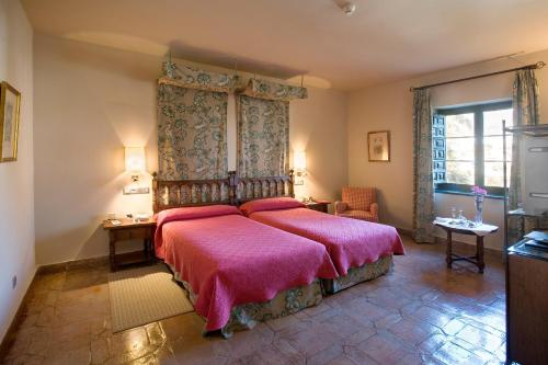 A bed or beds in a room at Parador de Jarandilla de la Vera