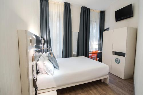 A bed or beds in a room at Petit Palace Canalejas Sevilla
