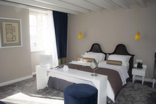 A bed or beds in a room at XII Century Heritage Hotel