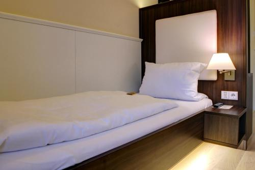 A bed or beds in a room at The Heidelberg Exzellenz Hotel