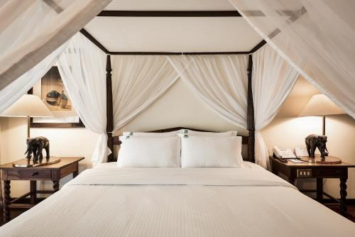 A bed or beds in a room at Safari Park Hotel