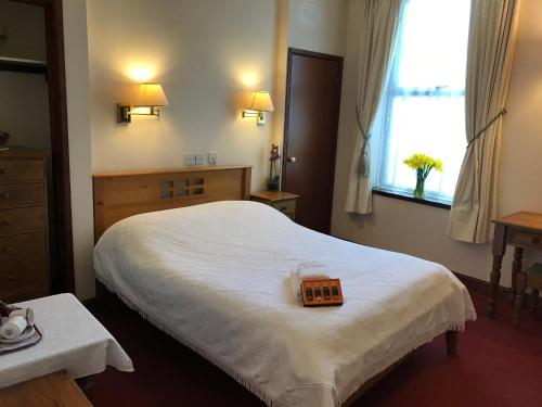 A bed or beds in a room at Garden Hotel
