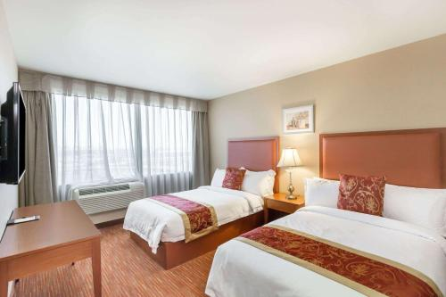 A bed or beds in a room at Ramada by Wyndham Flushing Queens