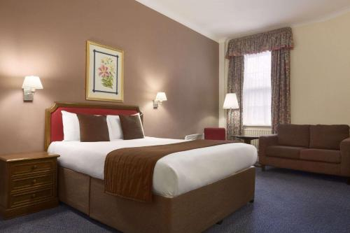 A bed or beds in a room at Ramada Crawley-Gatwick
