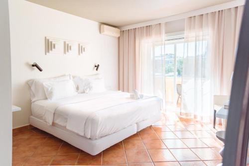 A bed or beds in a room at Costa d'Oiro Ambiance Village