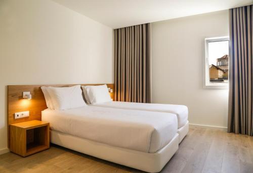 Een bed of bedden in een kamer bij Hotel Spot Family Suites