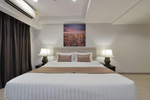 A bed or beds in a room at Aspira Residence Ruamrudee