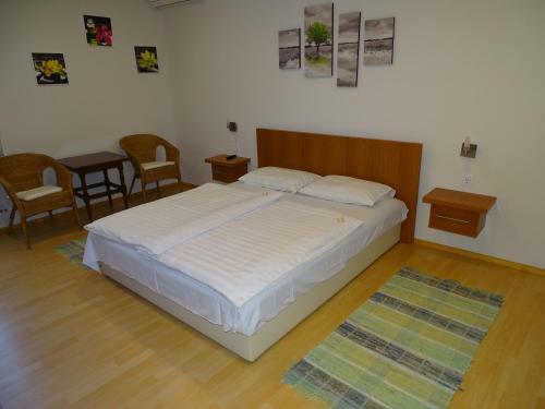 A bed or beds in a room at Alabárdos Panzió és Apartmanház
