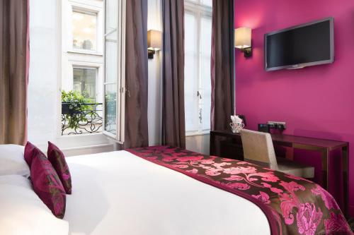 A bed or beds in a room at Hôtel Paris Louvre Opéra