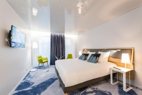 A bed or beds in a room at Seeko'o Hotel Bordeaux