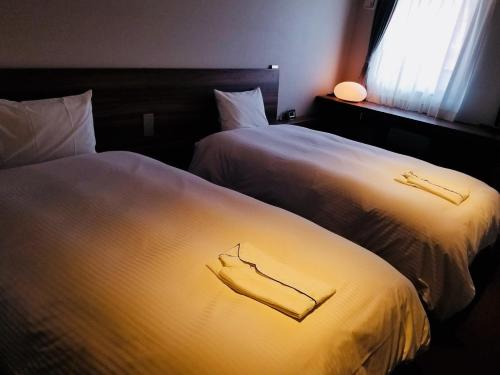 A bed or beds in a room at BRENZA HOTEL