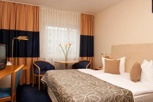 A bed or beds in a room at Tryp by Wyndham Bremen Airport
