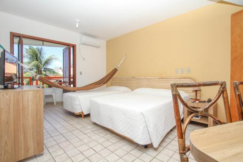 A bed or beds in a room at Marambaia Apart Hotel