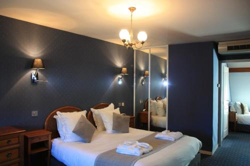 A bed or beds in a room at Hôtel Henry II Beaune Centre
