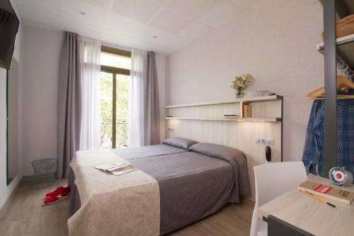 A bed or beds in a room at Hostal Benidorm