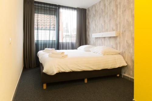 A bed or beds in a room at Beach Hotel Katwijk
