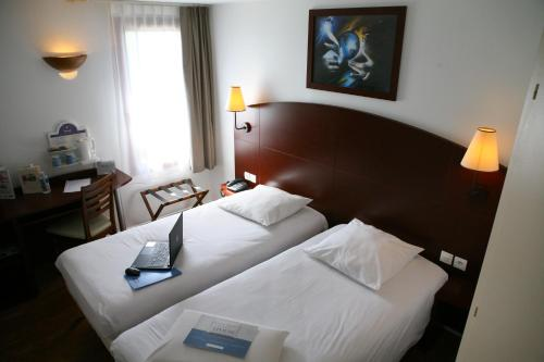 A bed or beds in a room at Kyriad Chateauroux
