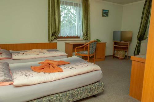 A bed or beds in a room at Pension zum Schwanenteich