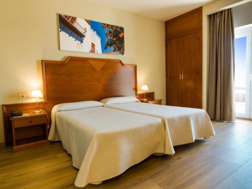 Säng eller sängar i ett rum på Hotel Monarque El Rodeo