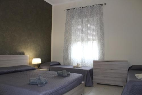 A bed or beds in a room at Cagliari 4u Self Catering