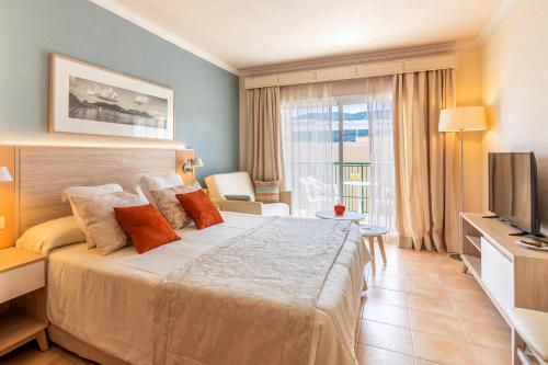 A bed or beds in a room at VIVA Cala Mesquida Resort & Spa
