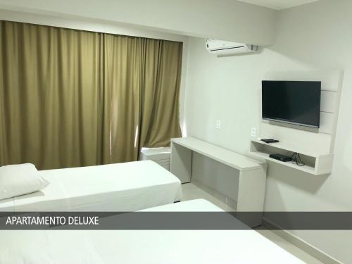 A television and/or entertainment centre at GET Apart Hotel - Garvey