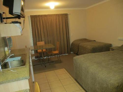 A bed or beds in a room at Tambo Mill Motel & Caravan Park