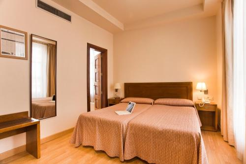 A bed or beds in a room at Hotel Granada Centro